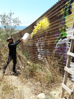 """Here Jim, throw this bucket of paint at the border fence!"" -Enrique to Jim. Playas de Tijuana"