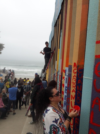 Gringo on a ladder. Border wall painting, Playas de Tijuana