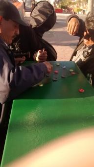 A few viejitos playing impromtu soda cap checkers atop an electrical box. Next to Monumental Reloj (the Tijuana Arch), Avenida Revolución, Tijuana